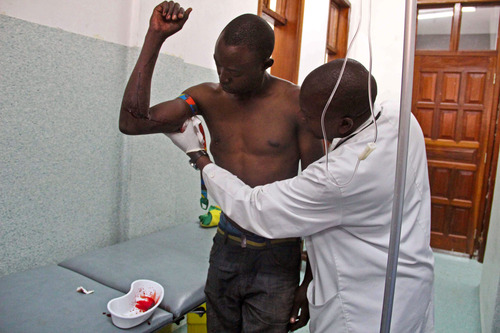 A young man, left,  wounded by bullets during fighting between the Congolese army and M23 rebels is treated at the Heal Africa hospital in Goma, Congo, Tuesday, Nov. 20, 2012. A rebel group created just seven months ago seized the strategic provincial capital of Goma, home to more than 1 million people in eastern Congo, and its international airport on Tuesday, officials and witnesses said, raising the specter of a regional war. (AP Photo/Melanie Gouby)