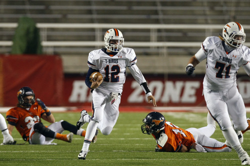 Chris Detrick  |  The Salt Lake Tribune Timpview's Jake Lloyd (12) runs past Mountain Crest's Gaje Fergeson (23) and Mountain Crest's Alex Huerta (12) during the second half of the 4A championship game at Rice-Eccles Stadium Friday November 16, 2012. Timpview defeated Mountain Crest 38-31