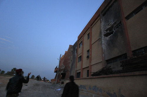 Syrian fighters stand guard in front of a destroyed building at a military base they took over from the Syrian army in Aleppo, Monday, Nov. 19, 2012. (AP Photo/ Khalil Hamra)