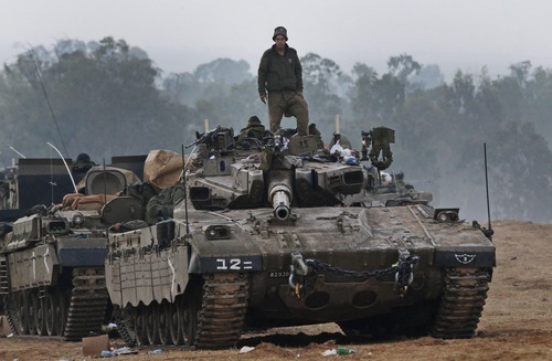 An Israeli soldier stands on a tank at a staging area near the Israel Gaza Strip Border, southern Israel, early Tuesday, Nov. 20, 2012. U.N. Secretary-General Ban Ki-moon is urging Israeli forces and Gaza militants to hold their fire, warning that a further escalation of the seven-day-old conflict would endanger the entire region. (AP Photo/Lefteris Pitarakis)