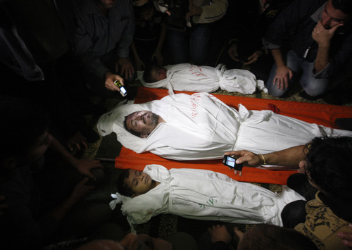 EDS NOTE: GRAPHIC CONTENT- Palestinian mourners gather around the bodies of Foud Hijazi, 45, and his sons Suhaib, 2, and Mohammed, 4, killed in an Israeli strike, during their funeral at a mosque in the Jebaliya refugee camp, in Gaza Strip, Tuesday, Nov. 20, 2012. Efforts to end a week-old convulsion of Israeli-Palestinian violence drew in the world's top diplomats on Tuesday, with President Barack Obama dispatching his secretary of state to the region on an emergency mission and the U.N. chief appealing from Cairo for an immediate cease-fire. (AP Photo/Hatem Moussa)