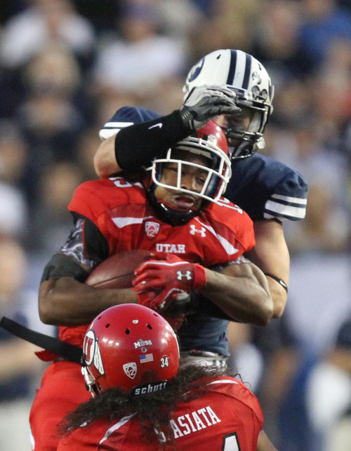 Rick Egan | Tribune file photo  Utes running back John White IV (15) is brought down by BYU linebacker Brandon Ogletree (44) during Utah's game against BYU at Lavell Edwards Stadium in Provo on Sept. 17, 2011.