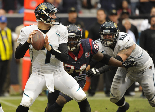 Houston Texans Antonio Smith, center, bears down on Jacksonville Jaguars' Chad Henne, left, as Mike Brewster (60) tries to block during the fourth quarter of an NFL football game against the Jacksonville Jaguars, Sunday, Nov. 18, 2012, in Houston. (AP Photo/Dave Einsel)