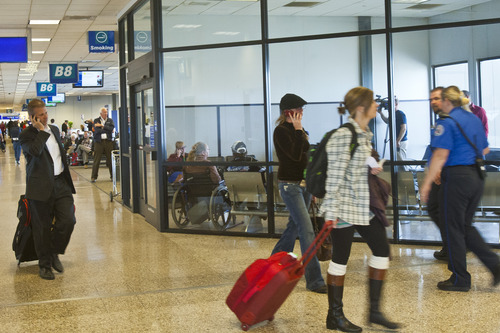 Chris Detrick  |  The Salt Lake Tribune Travelers walk past a smoking lounge at the Salt Lake City International Airport on Tuesday -- the day a national health study was released criticizing such designated smoking areas.