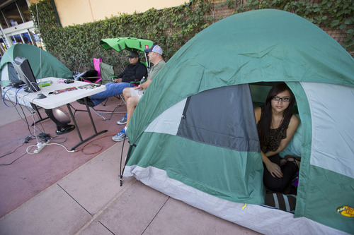 Mary Gallardo, 22 from Tempe, sits in her tent while waiting in line for Black Friday deals outside Best Buy at Tempe Marketplace in Tempe. Ariz., Tuesday, Nov. 20 2012. Gallardo has been waiting since Monday night. She said she drove by the store all day Monday looking for a line and when she saw someone line up, she said had to do it too. She plans on buying TVs. (AP Photo/The Arizona Republic, Michael Chow)