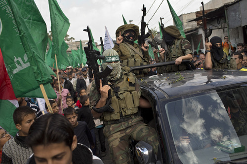 Palestinian Hamas militants parade during a rally to celebrate the Israel-Hamas cease-fire in the Jebaliya refugee camp, north Gaza Strip, Thursday, Nov. 22, 2012. Gaza residents cleared rubble and claimed victory on Thursday, just hours after an Egyptian-brokered truce between Israel and Gaza's Hamas rulers ended the worst cross-border fighting in four years. (AP Photo/Bernat Armangue)
