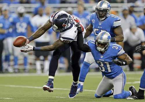 Houston Texans wide receiver Andre Johnson (80) loses control of the ball after a hit by Detroit Lions cornerback Drayton Florence (31) during the first quarter of an NFL football game at Ford Field in Detroit, Thursday, Nov. 22, 2012. The pass fell incomplete. (AP Photo/Paul Sancya)