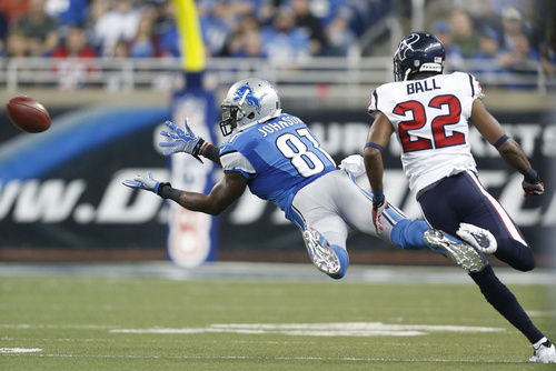 Detroit Lions wide receiver Calvin Johnson (81) makes a diving catch as Houston Texans defensive back Alan Ball (22) defends during the first quarter of an NFL football game at Ford Field in Detroit, Thursday, Nov. 22, 2012. (AP Photo/Rick Osentoski)