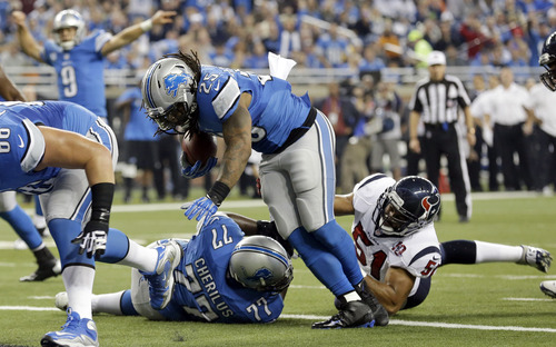 Detroit Lions running back Mikel Leshoure (25) scores a touchdown during the first quarter of an NFL football game against the Houston Texans at Ford Field in Detroit, Thursday, Nov. 22, 2012. (AP Photo/Paul Sancya)