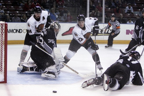 Kim Raff | The Salt Lake Tribune Utah Grizzlies players (left) Riley Armstrong and (right) Bryan Cameron miss a shot at goal as Idaho Steelheads goalie Tyler Beskorowany looks on during the Grizzlies home opener at the Maverick Center in West Valley City, Utah on October 13, 2012.