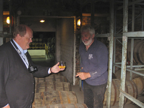 The Rev. Michael Mayor samples whiskey straight from a cask in the Bruichladdich warehouse with Distillery Manager Duncan McGillivray. Courtesy Michael Mayor