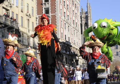 Costumed characters and a marching band precede the Kermit The Frog balloon on New York's Central Park West during the 86th annual Macy's Thanksgiving Day Parade,Thursday, Nov 22, 2012. (AP Photo/ Louis Lanzano)