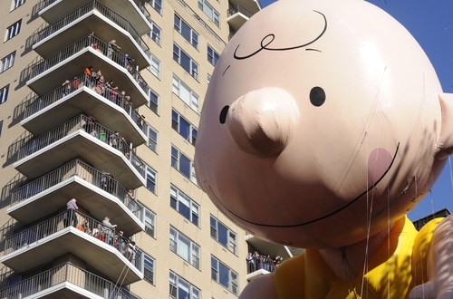 The Charlie Brown balloon passes people on balconies on New York's Central Park West during the 86th annual Macy's Thanksgiving Day Parade,Thursday, Nov 22, 2012. (AP Photo/ Louis Lanzano)