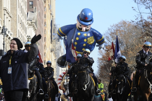 Mounted police lead a  policeman balloon as it makes its way down New York's Central Park West in the 86th annual Macy's Thanksgiving Day Parade,Thursday, Nov 22, 2012. (AP Photo/ Louis Lanzano)