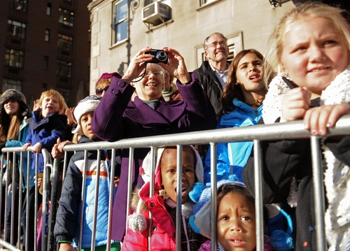 Spectators line the sidewalk as balloons and bands make their way down New York's Central Park West in the 86th annual Macy's Thanksgiving Day Parade,Thursday, Nov 22, 2012. (AP Photo/ Louis Lanzano)
