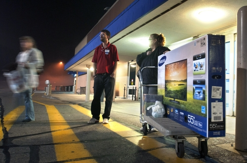Kris Chicky, right, waits with the 55-inch T.V. she bought shortly after the store's 6AM sale began on Thanksgiving Day, Thursday, Nov. 22, 2012, in Grand Rapids, Mich. Stores typically open in the wee hours of the morning on the day after Thanksgiving known as Black Friday, named for the period when stores traditionally turn a profit for the year. But Black Friday openings have crept earlier and earlier over the past few years. Now, stores from Wal-Mart to Toys R Us are opening their doors on Thanksgiving evening, hoping Americans will be willing to shop soon after they finish their pumpkin pie. (AP Photo/The Grand Rapids Press, Chris Clark ) ALL LOCAL TV OUT; LOCAL TV INTERNET OUT
