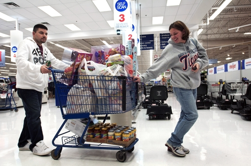 Jeremy and Rebecca Wheeler guide their full cart out of a Meijer, in Grand Rapids, Mich., shortly after the store's 6AM sale began on Thanksgiving Day, Thursday, Nov. 22, 2012.  Her mother, Pat Brakla, checks out behind her. Stores typically open in the wee hours of the morning on the day after Thanksgiving known as Black Friday, named for the period when stores traditionally turn a profit for the year. But Black Friday openings have crept earlier and earlier over the past few years. Now, stores from Wal-Mart to Toys R Us are opening their doors on Thanksgiving evening, hoping Americans will be willing to shop soon after they finish their pumpkin pie.(AP Photo/The Grand Rapids Press, Chris Clark ) ALL LOCAL TV OUT; LOCAL TV INTERNET OUT