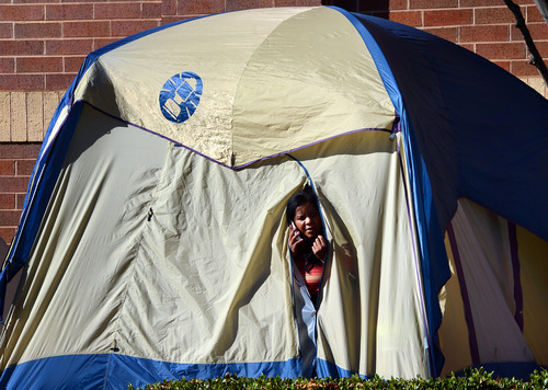 Beth Collins, of Garner peeks out from her tent on Thanksgiving morning as she waits in line in front of the Best Buy in Garner, N.C. Stores typically open in the wee hours of the morning on the day after Thanksgiving known as Black Friday, named for the period when stores traditionally turn a profit for the year. But Black Friday openings have crept earlier and earlier over the past few years. Now, stores from Wal-Mart to Toys R Us are opening their doors on Thanksgiving evening, hoping Americans will be willing to shop soon after they finish their pumpkin pie. (AP Photo/The News & Observer , Chuck Liddy)