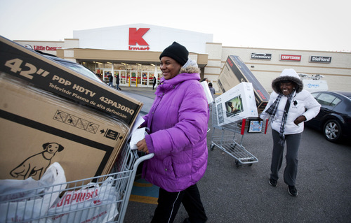 IMAGE DISTRIBUTED FOR KMART - Customers Soalina Agers, left, and Val Gray, both from Chicago, walk through the Kmart parking lot with their pre-Black Friday deals at the Addison Street store in Chicago on Thanksgiving Thursday, Nov. 22, 2012. Kmart was the first major retailer nationwide to kick off pre-Black Friday shopping on Thanksgiving morning at 6 a.m.  (John Konstantaras/AP Images for Kmart)