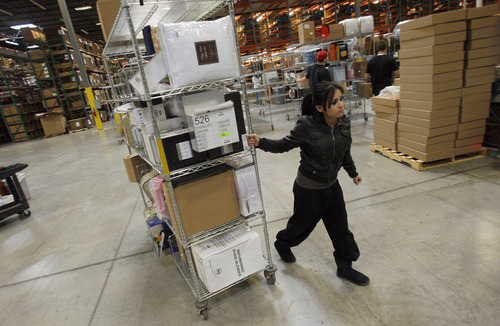 Francisco Kjolseth  |  The Salt Lake Tribune Selina Haro, pulls a cart full of product as she looks for an open bay to package the online orders at Overstock.com's distribution center in Salt Lake City the day after Thanksgiving on Friday, November 23, 2012.