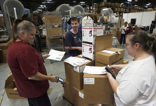 Francisco Kjolseth  |  The Salt Lake Tribune Employees at Overstock.com's distribution center in Salt Lake City, Christi Wigginton, Jayson Cuddy (cq) and Margaret Feek, from left, get orders ready for packaging at the company's warehouse in Salt Lake City on Friday, November 23, 2012.