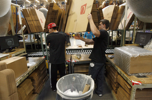 Francisco Kjolseth  |  The Salt Lake Tribune Employees at Overstock.com's distribution center in Salt Lake City, Brandon Dmochowski, left, and Nathan Stephens speed through online shipping orders the day after Thanksgiving as the company runs 24hrs a day, seven days a week with the holiday season in full swing.