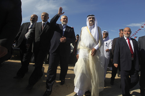FILE- In this Tuesday, Oct. 23, 2012 file photo, the Emir of Qatar Sheik Hamad bin Khalifa al-Thani, second right, and Gaza's Hamas Prime minister Ismail Haniyeh, third left, arrive for the corner-stone laying ceremony of a new center providing artificial limbs, in Bait Lahiya, northern Gaza Strip. (AP Photo/Ali Ali, Pool, File)