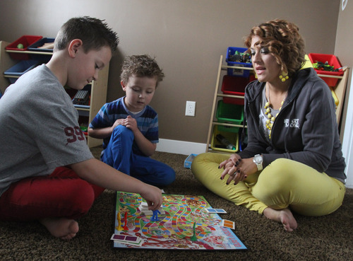 Rick Egan  | The Salt Lake Tribune  Mason Pettit, 7, plays Candyland with his 4-year-old brother Teagan, and his mother, Brytten Pettit, in their West Jordan home. Teagan was born seemingly healthy but was diagnosed days later with a heart defect. Utah is studying how to screen newborns for seven heart defects, including the one threatening Teagan's health.