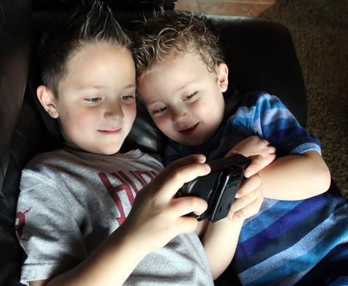 Rick Egan  | The Salt Lake Tribune   Mason Pettit, 7, left, plays a video game with his brother Teagan, 4, (right) in their West Jordan home. Utah is studying how to screen newborns for seven heart defects, including the one threatening Teagan's health.