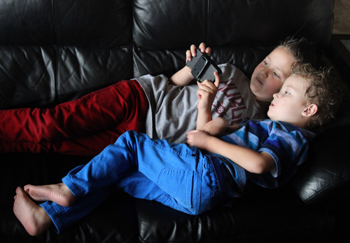 Rick Egan  | The Salt Lake Tribune  Mason Pettit, 7, top, plays a video game with his brother Teagan, 4, in their West Jordan home. Utah is studying how to screen newborns for seven heart defects, including the one threatening Teagan's health.