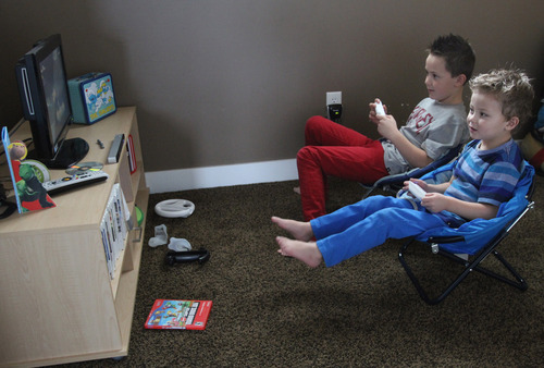 Rick Egan  | The Salt Lake Tribune  Mason Pettit, 7 (top) plays a video game with his brother Teagan, 4, in their West Jordan home. Teagan was born seemingly healthy but was diagnosed days later with a heart defect. Utah is studying how to screen newborns for seven heart defects, including the one threatening Teagan's health.