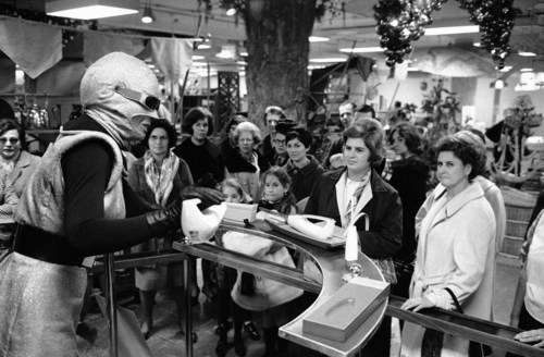 """Roberta the Robot demonstrates an electric carving knife to Christmas shoppers in the Macy's department store basement in New York, Nov. 17, 1966. Woman at right watches with critical eyes but the two little girls appear to be in a state of wonderment. Roberta's actions are controlled by an operator at the other end of the """"apron string"""" seen on the floor at the lower left. (AP Photo/Eddie Adams)"""