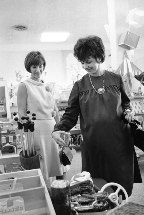 Mrs. Marilyn Lovell, wife of the pilot of Gemini 7 spacecraft, right, looks at childrenís jumping shoes as she shops for Christmas toys in Houston, Texas, Dec. 10, 1965. Accompanying Mrs. Lovell is Mrs. Charles Conrad, wife of the astronaut who was pilot on the Gemini 5 flight. (AP Photo/Ed Kolenovsky)