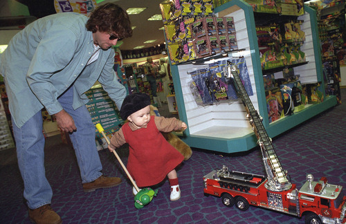 Jerome Peri and his 11-month-old daughter, Manon, test the toys at FAO Schwartz in the Beverly Center Mall in West Hollywood, Calif., Nov. 24, 1995. The Periís are among the early holiday shoppers trying to beat the larger crowds that appear later in the Christmas season. (AP Photo/Rhonda Birndorf)