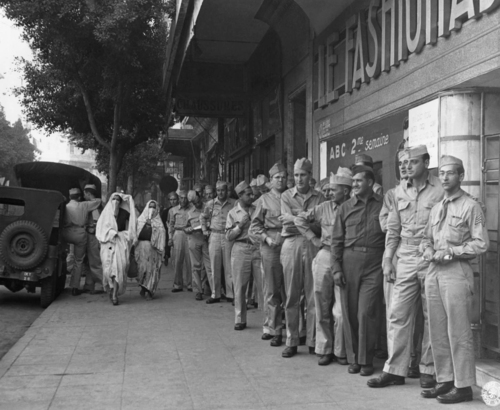 """On the opening day of the gift sale, U.S.soldiers  lined up outside the shop """"La Fashionable"""" on Oct. 8, 1943, which was in temporary use as a Post Exchange. When the doors opened there was a grand rush to buy native North African merchandise to send home as Christmas presents. Native woman  walking along the street . (AP Photo)"""
