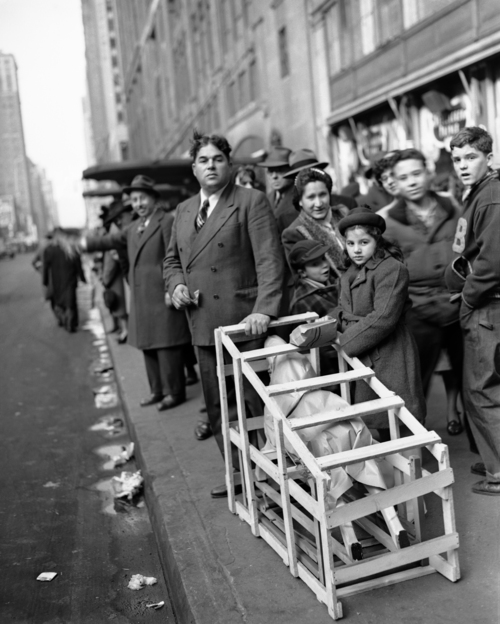 A Christmas Eve shopper with a crated rocking horse tries to hail a cab outside Macy's department store in New York City on Dec. 24, 1946. (AP Photo/Carl Nesensohn)