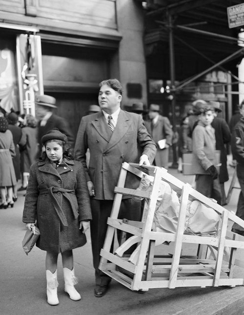 A Christmas Eve shopper with his daughter and a crated rocking horse tries to hail a cab outside Macy's department store in New York,  Dec. 24, 1946. (AP Photo/Carl Nesensohn)