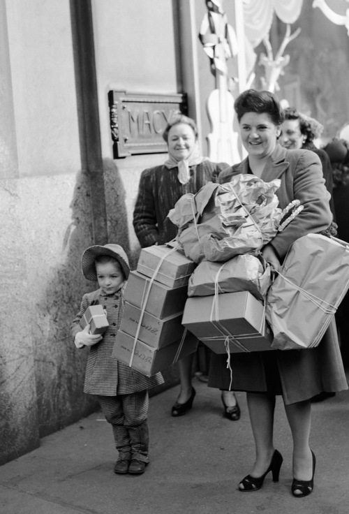 """Mrs. Frances Corless her daughter """"Chickie"""" are loaded down with bundles after doing some last minute shopping at Macy's on Christmas Eve in New York, Dec. 24, 1946. (AP PhotoCarl Nesensohn)"""