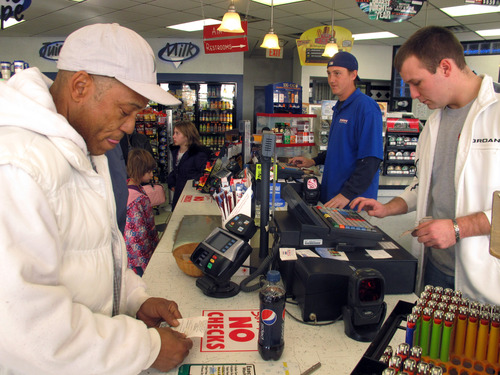 Michael Arrington, left, buys a Powerball ticket from cashier Lee Heilig, right, on Friday, Nov. 23, 2012, at a DeliMart convenience store in Iowa City, Iowa. The jackpot had reached $325 million as of Friday. (AP Photo/Grant Schulte)
