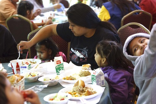 Leah Hogsten  |  The Salt Lake Tribune Shelter resident Nina Reed feeds her daughter Alexandra, 2, left, as her daughter Joline, 3, and son Santino, 7, enjoy their Thanksgiving meal. Over 250 volunteers and parishioners at the Holy Trinity Green Orthodox Cathedral serve Thanksgiving dinner to people in need, which included a clothing and food donation drive, Thursday, November 22, 2012 in Salt Lake City.