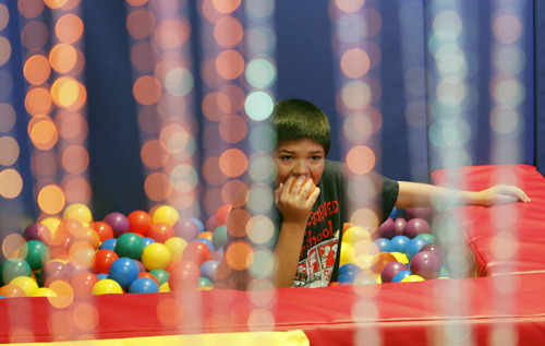Al Hartmann  |  The Salt Lake Tribune A student immerses himself in the tactile security of a large bin of rubber balls in the sensory room at Whittier Elementary School. The school has a unique special needs wrap-around service hub that features a sensory room and a physical therapy room to accomodate the needs of Whittier's disabled students.