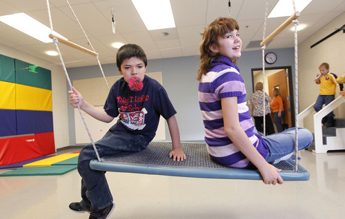 Al Hartmann  |  The Salt Lake Tribune Students ride on a swing in the physical therapy room at Whittier Elementary School. The school has a unique special needs wrap-around service hub that features a sensory room and a physical therapy room to accomodate the needs of Whittier's disabled students.