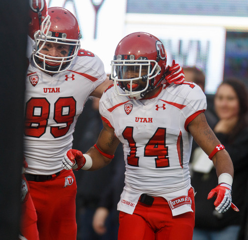 Trent Nelson  |  The Salt Lake Tribune Utah Utes wide receiver Reggie Dunn (14) celebrates his touchdown in the fourth quarter as the Colorado Buffaloes host the University of Utah Utes, college football Friday November 23, 2012 in Boulder. At left is Utah Utes tight end Dallin Rogers (89).