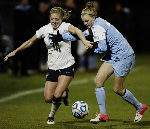 Brigham Young's Carlee Payne Holmoe (7) struggles for the ball with North Carolina's Hanna Gardner during an NCAA college Elite Eight soccer tournament game in Provo, Utah on Friday, Nov. 23, 2012. (AP Photo/The Daily Herald, Jim McAuley)