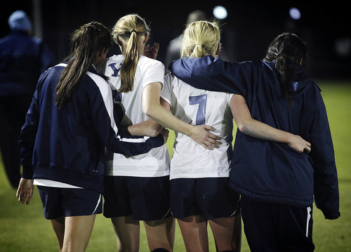Brigham Young players walk of the field arm-in-arm after losing to North Carolina after an NCAA college Elite Eight soccer tournament game in Provo, Utah on Friday, Nov. 23, 2012. (AP Photo/The Daily Herald, Jim McAuley)