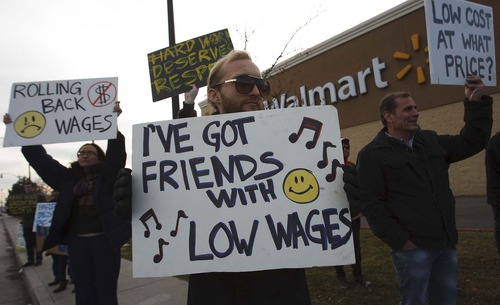 Leah Hogsten  |  The Salt Lake Tribune Stewart Thorpe (center) protests Walmart's low wages on behalf of his two friends who work at other locations in the Salt Lake Valley.      Friends and family of Walmart employees protested working conditions during a Walmart Workers Walkout Solidarity Rally on Black Friday at the Walmart located at 300 West and 1300 South, Salt Lake City Friday November 23, 2012 in Salt Lake City.