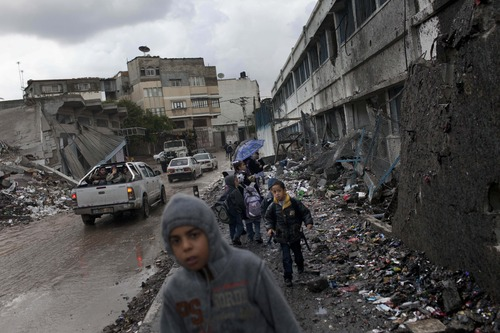 Palestinian schoolchildren walk by a damaged school, right, in Gaza City, Saturday, Nov. 24, 2012. Schools in Gaza opened Saturday for the first time since the truce, which calls for an end to Gaza rocket fire on Israel and Israeli airstrikes on Gaza, came after eight days of cross-border fighting, the bloodiest between Israel and Hamas in four years. The school was damaged when Israeli forces struck on a nearby building. (AP Photo/Bernat Armangue)