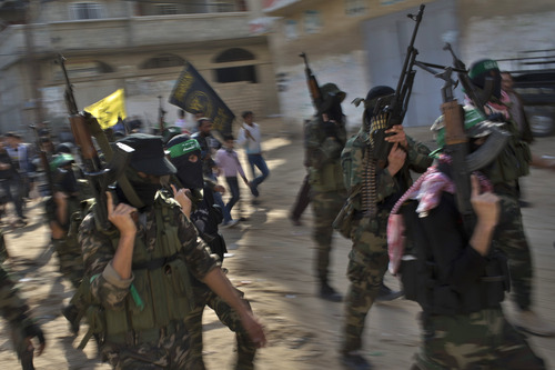 Hamas militants of the Izzedine al-Qassam Brigades attend the funeral of Hamas member Joudeh Shamallah in Gaza City, Saturday, Nov. 24, 2012. According to family members Shamallah was badly injured during the latest Israeli-Hamas fight and died from wounds Saturday. (AP Photo/Bernat Armangue)