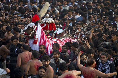 Pakistani Shiite Muslims touch a horse, to symbolize the horse that carried Imam Hussein during the battle of Karbala, to pay tribute during a Muharram procession in Islamabad, Pakistan on Saturday, Nov. 24, 2012. Muharram is a month of mourning in remembrance of the martyrdom of Imam Hussein, the grandson of Prophet Mohammed. (AP Photo/Anjum Naveed)