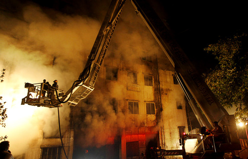 Bangladeshi firefighters battle a fire at a garment factory in the Savar neighborhood in Dhaka, Bangladesh, late Saturday, Nov. 24, 2012. At least 112 people were killed in a fire that raced through the multi-story garment factory just outside of Bangladesh's capital, an official said Sunday. (AP Photo/Hasan Raza)